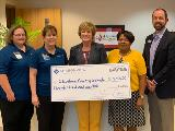Sharonview delivers check to Cleveland County Schools