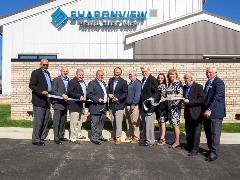 image of Sharonview staff and board of directors cutting ribbon at ceremony
